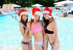 3 сексуальных девушки в бикини и красных крышках рождества Стоковые Изображения