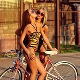 2 сексуальных женщины в купальниках с винтажным велосипедом Стоковая Фотография