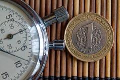 Секундомер и монетка с деноминацией 1 турецкой лиры на предпосылке деревянного стола Стоковые Фото