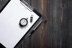 Секундомер, ручка и пусковая площадка на деревянном модель-макете copyspace взгляд сверху предпосылки Стоковое Фото