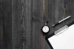 Секундомер, ручка и пусковая площадка на деревянном copyspace взгляд сверху предпосылки Стоковые Изображения