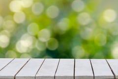 селективная зеленого цвета фокуса предпосылки естественная Зеленая предпосылка имеет лист и траву bokeh на белом деревянном поле  стоковые изображения