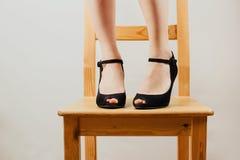 Селективная съемка ног ` s белой женщины в черном максимуме накренила ботинки стоя на деревянном стуле стоковые изображения