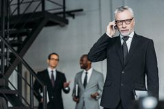 селективный фокус бизнесмена говоря на smartphone с коллегами позади Стоковая Фотография RF