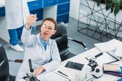 селективный фокус женского исследователя смотря трубку с реагентом в руке с коллегой позади Стоковые Изображения