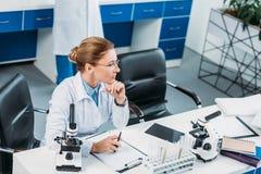селективный фокус задумчивого женского исследователя на рабочем месте с коллегой позади Стоковое Изображение RF