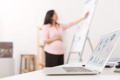 Селективный фокус компьтер-книжки с беременной женщиной на заднем плане Стоковые Фотографии RF