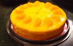 Селективный фокус на десерте хлебопекарни, оранжевом торте цвета с оранжевым муссом и оранжевых отбензиниваниях плодоовощ на черн Стоковые Изображения