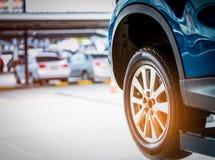 Селективный фокус на колесе голубого автомобиля SUV заднем на запачканной предпосылке Автомобиль с новой автошиной высокой эффект Стоковое Изображение RF