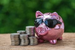 Селективный фокус на лоснистой розовой копилке с стогом монеток как Стоковое Изображение