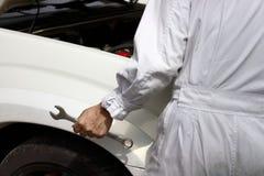 Селективный фокус на руках профессионального ключа удерживания человека механика с автомобилем в открытом клобуке на предпосылке  Стоковые Фото