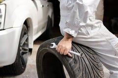 Селективный фокус на руках профессионального механика в форме сидя на автошине и держа ключ на предпосылке гаража ремонта Стоковое фото RF