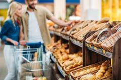 селективный фокус пар при магазинная тележкаа ходя по магазинам совместно стоковые изображения rf