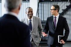 селективный фокус усмехаясь multiracial бизнесменов имея переговор пока идущ стоковое фото
