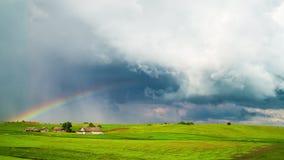Сельские ландшафт, дождевые облако и радуга, промежуток времени сток-видео