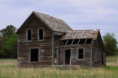 Сельский покинутый дом фермы окруженный травой прерии стоковая фотография rf