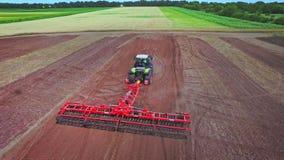 Сельскохозяйственная техника работая на аграрном поле вспахивать поля видеоматериал