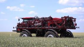 Сельскохозяйственная техника, самоходный спрейер управляет на зеленом поле сток-видео