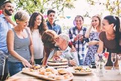 Семейное торжество или приём гостей в саду снаружи в задворк стоковое изображение