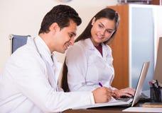 Семейные врачи при стетоскоп работая в офисе совместно Стоковое Изображение RF