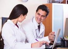 Семейные врачи при стетоскоп работая в офисе совместно Стоковое Фото