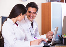 Семейные врачи при стетоскоп работая в офисе совместно Стоковые Фото