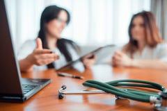 Семейный врач, молодая жена разговаривает с специалистом Стоковое Изображение