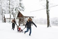 Семейный отдых на выходных outdoors Маленькие ребеята наслаждаются ездой саней Sledding ребенка Стоковая Фотография