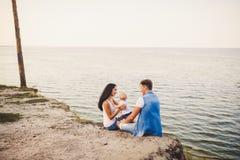 Семейный отдых темы с малым ребенком на природе и море Мама, папа и дочь одного года сидят в объятии, девушках в t Стоковое Изображение