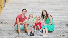 Семейный отдых в Европе Родители и дети при touristic карта ища привлекательности сток-видео