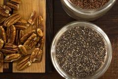 Семена в контейнере около разделочной доски, пеканы Chia, семена льна Стоковые Фотографии RF