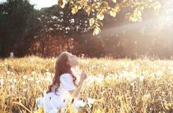 Семена девушки дуя от одуванчика цветка в осени Стоковые Изображения RF