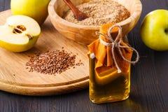 Семена льна Брайна в масле ложки и льняного семени в стеклянной бутылке на белой деревянной предпосылке Масло льна богато в жирно стоковое фото
