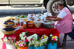 Семена, мед и цветки продаж женщины Стоковая Фотография