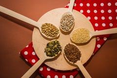 Семена на деревянных ложках которые лежат на круглой разделочной доске и красной салфетке - сезаме, льняном семени, тыкве и семен Стоковые Изображения