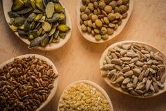 Семена на деревянных ложках которые лежат на разделочной доске - сезаме, льняном семени, тыкве и семенах подсолнуха, зеленых чече Стоковые Фото