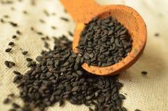 Семена сезама черноты ложки конца-вверх макроса деревянные стоковое фото
