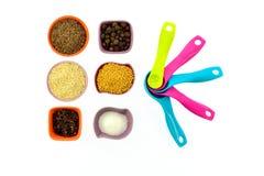 Семена, специи, зерна в малых пестротканых чашках и измеряя ложки Стоковые Фотографии RF