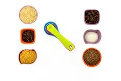 Семена, специи, зерна в малых пестротканых чашках и измеряя ложки Стоковые Изображения