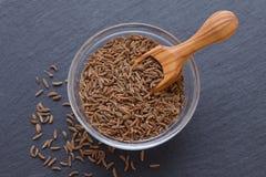 Семена тимона, тмина в шаре и деревянного ветроуловителя на черной предпосылке Стоковые Изображения