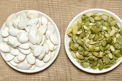 Семена тыквы в плите, на деревянной предпосылке Стоковая Фотография RF