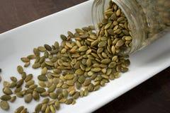 Семена тыквы разливая из контейнера, посоленное, близкое поднимающего вверх Стоковое Изображение