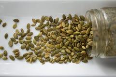 Семена тыквы разливая из контейнера, сверху, близко Стоковое Изображение RF