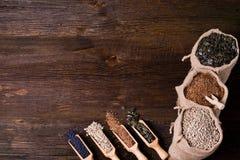 Семена тыквы, солнцецвет и семена льна в деревянной ложке На заднем плане сумка джута с семенами Стоковые Изображения RF