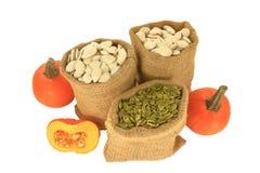 Семена тыквы с и без раковины в сумках мешковины, тыквах Стоковые Фото