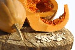 Семена тыкв и тыкв на деревянной и белой предпосылке стоковое фото rf