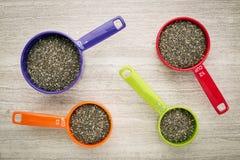 Семена Chia в измеряя чашках Стоковые Фотографии RF