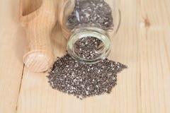 Семена Chia разливая из стеклянной бутылки Стоковое фото RF