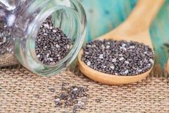 Семена Chia разливая из стеклянной бутылки Стоковые Фотографии RF
