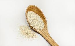 Семена Sesam с деревянной ложкой на белой предпосылке стоковая фотография